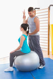 Trainer assisting woman exercising on fitness ball Royalty Free Stock Photography