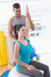 Trainer assisting woman exercising on fitness ball Royalty Free Stock Images