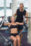 Trainer assisting woman on fitness machine at gym. Smiling male trainer assisting women on fitness machine at the gym Stock Image