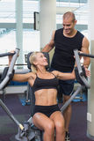 Trainer assisting woman on fitness machine at gym. Smiling male trainer assisting women on fitness machine at the gym Royalty Free Stock Photo