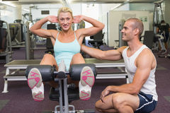 Trainer assisting woman on fitness machine at gym. Smiling male trainer assisting women on fitness machine at the gym Stock Photos