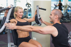 Trainer assisting woman on fitness machine at gym Stock Photography
