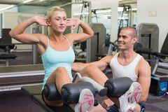 Trainer assisting woman on fitness machine at gym. Smiling male trainer assisting women on fitness machine at the gym Royalty Free Stock Photos