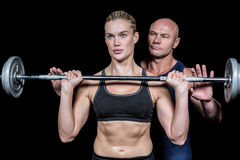 Trainer assisting woman for lifting crossfit. Trainer assisting women for lifting crossfit against black background Stock Photos