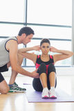 Trainer assisting woman with pilate exercises in fitness studio. Male trainer assisting young women with pilate exercises in the fitness studio Royalty Free Stock Images