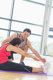 Trainer assisting woman with pilate exercises in fitness studio. Side view of a male trainer assisting young women with pilate exercises in the fitness studio Royalty Free Stock Images