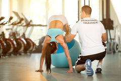 Trainer assisting woman on pilates ball Stock Image