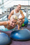Trainer assisting woman with push ups at gym. View of a male trainer assisting women with push ups at the gym Stock Photos