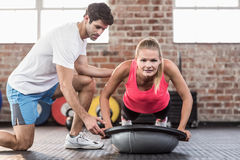 Trainer assisting woman with push ups at gym. View of a male trainer assisting women with push ups at the gym Royalty Free Stock Photo
