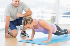 Trainer assisting woman with push ups. Male trainer assisting women with push ups in fitness studio Royalty Free Stock Photo