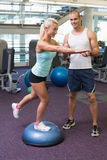 Trainer assisting woman with stretching exercises at gym. Smiling male trainer assisting women with stretching exercises at the gym Royalty Free Stock Images