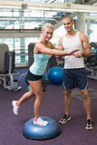 Trainer assisting woman with stretching exercises at gym. Smiling male trainer assisting women with stretching exercises at the gym Stock Image