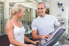 Trainer assisting woman with treadmill screen options at gym Stock Photo