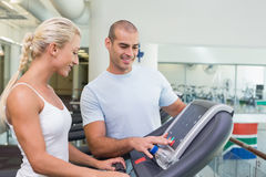 Trainer assisting woman with treadmill screen options at gym. View of a male trainer assisting women with treadmill screen options at the gym Royalty Free Stock Photo
