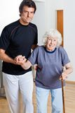 Trainer Assisting Woman With Walking Stick Stock Photo