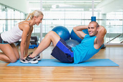 Trainer assisting young man with abdominal crunches at fitness studio. Side view of a female trainer assisting young men with abdominal crunches at fitness Stock Photo