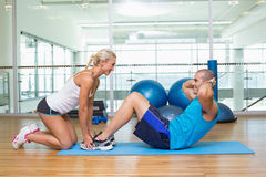 Trainer assisting young man with abdominal crunches at fitness studio. Side view of a female trainer assisting young men with abdominal crunches at fitness Stock Photos