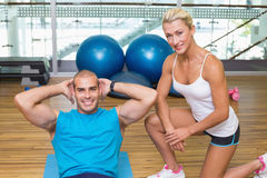 Trainer assisting young man with abdominal crunches at fitness studio. Smiling female trainer assisting young men with abdominal crunches at fitness studio Stock Photo