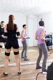 Trainer assists female athlete to make gymnastic tourniquet exer. Cises, supported with electric muscle stimulation purposed to increase effectiveness of Royalty Free Stock Photography