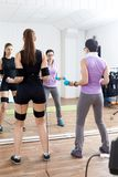 Trainer assists female athlete to make gymnastic tourniquet exer. Cises, supported with electric muscle stimulation purposed to increase effectiveness of Royalty Free Stock Photo