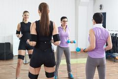 Trainer assists female athlete to make gymnastic tourniquet exer. Cises, supported with electric muscle stimulation purposed to increase effectiveness of Stock Photo