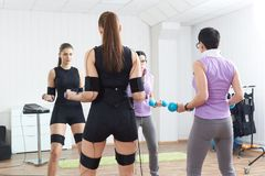 Trainer assists female athlete to make gymnastic tourniquet exer. Cises, supported with electric muscle stimulation purposed to increase effectiveness of Royalty Free Stock Images