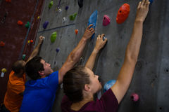 Trainer with athletes climbing wall in healthy club Stock Photos