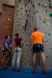 Trainer with athletes standing by climbing wall at gym Royalty Free Stock Images