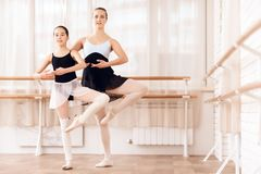 The trainer of the ballet school helps young ballerina perform different choreographic exercises. stock image