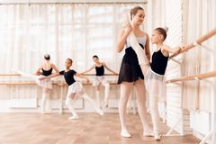 The trainer of the ballet school helps young ballerina perform different choreographic exercises. royalty free stock image