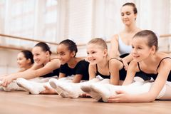 The trainer of the ballet school helps young ballerinas perform different choreographic exercises. royalty free stock photography