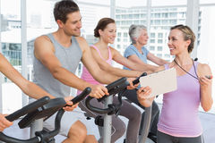 Trainer besides people working out at spinning class Royalty Free Stock Photo