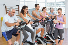 Trainer besides people working out at spinning class Stock Photography