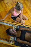 Trainer bijwonende vrouw met pilates op hervormer stock foto