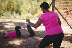 Trainer bijwonende vrouw terwijl het uitoefenen tijdens hinderniscursus stock fotografie