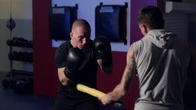 Trainer bildet Boxer in der Turnhalle aus, arbeitet Tritt und Verteidigung, Zeitlupe aus stock video footage