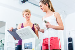 Trainer with body fat scale in gym Stock Photo