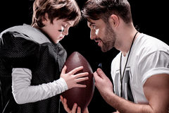 Trainer and boy with rugby ball standing face to face on black. Side view of trainer and boy with rugby ball standing face to face on black stock images