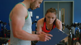Trainer with client on exercise bike stock video footage