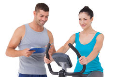 Trainer with client on exercise bike. On white background Stock Photo
