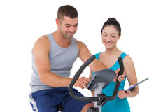 Trainer with client on exercise bike. On white background Stock Photography