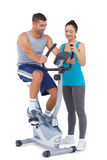 Trainer with client on exercise bike. On white background Royalty Free Stock Image