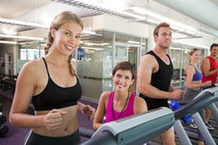 Trainer and clients smiling at camera on the treadmill Royalty Free Stock Images