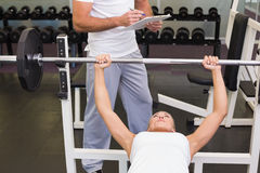 Trainer with clipboard besides woman lifting barbell in gym Royalty Free Stock Image