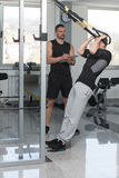 Trainer With Clipboard Man On Trx Fitness Straps Stock Image