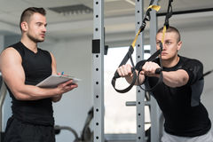 Trainer With Clipboard Man On Trx Fitness Straps Stock Photo