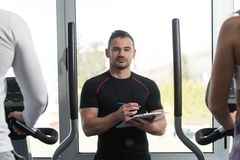 Trainer With Clipboard Monitors People While They Running Royalty Free Stock Images