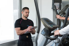 Trainer With Clipboard Monitors People While They Running Stock Photos