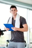 Trainer with clipboard standing in a bright gym. Portrait of a smiling male trainer with clipboard standing in a bright gym Stock Images