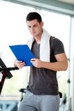 Trainer with clipboard standing in a bright gym Stock Photography